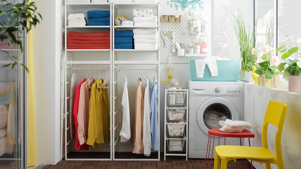 Waschküche mit dem JONAXEL Regal mit Kleiderstange sowie gefalteten Handtüchern und hängender Kleidung