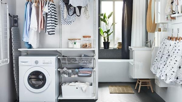 Waschküche mit weißen Einrichtungsschränken, Waschmaschine & viel Stauraum für Wäsche.
