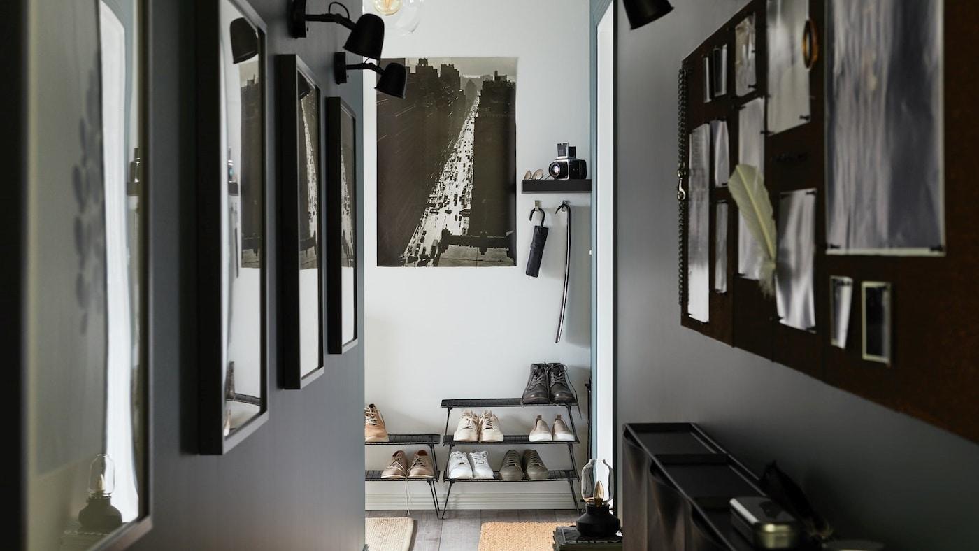 Wąski korytarz ze zdjęciami na ścianach, czarnymi drucianymi półkami na buty ustawionymi jedna na drugiej i czarną tablicą na notatki.