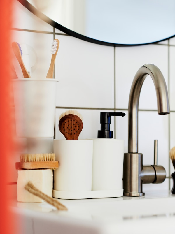 Water tap in a white-tiled bathroom with a STORAVAN three-piece set and accessories placed along the side of the washbasin.