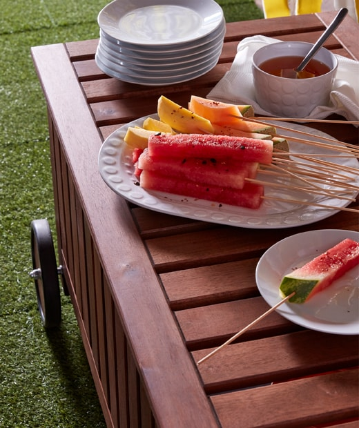 Watermelon and mango slices put on IKEA GRILLTIDER bamboo skewers on a big, white plate.