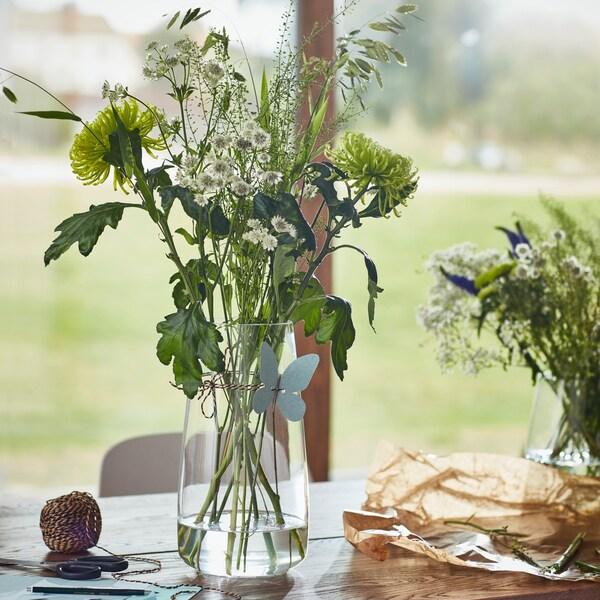 Wazon ze szkła z kwiatami stojący na drewnianym stole przy oknie.