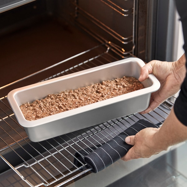 We see a mould containing homemade dough being put into the oven
