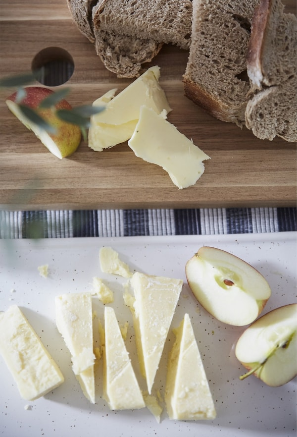 Wedges of cheese, apple and bread on chopping boards.