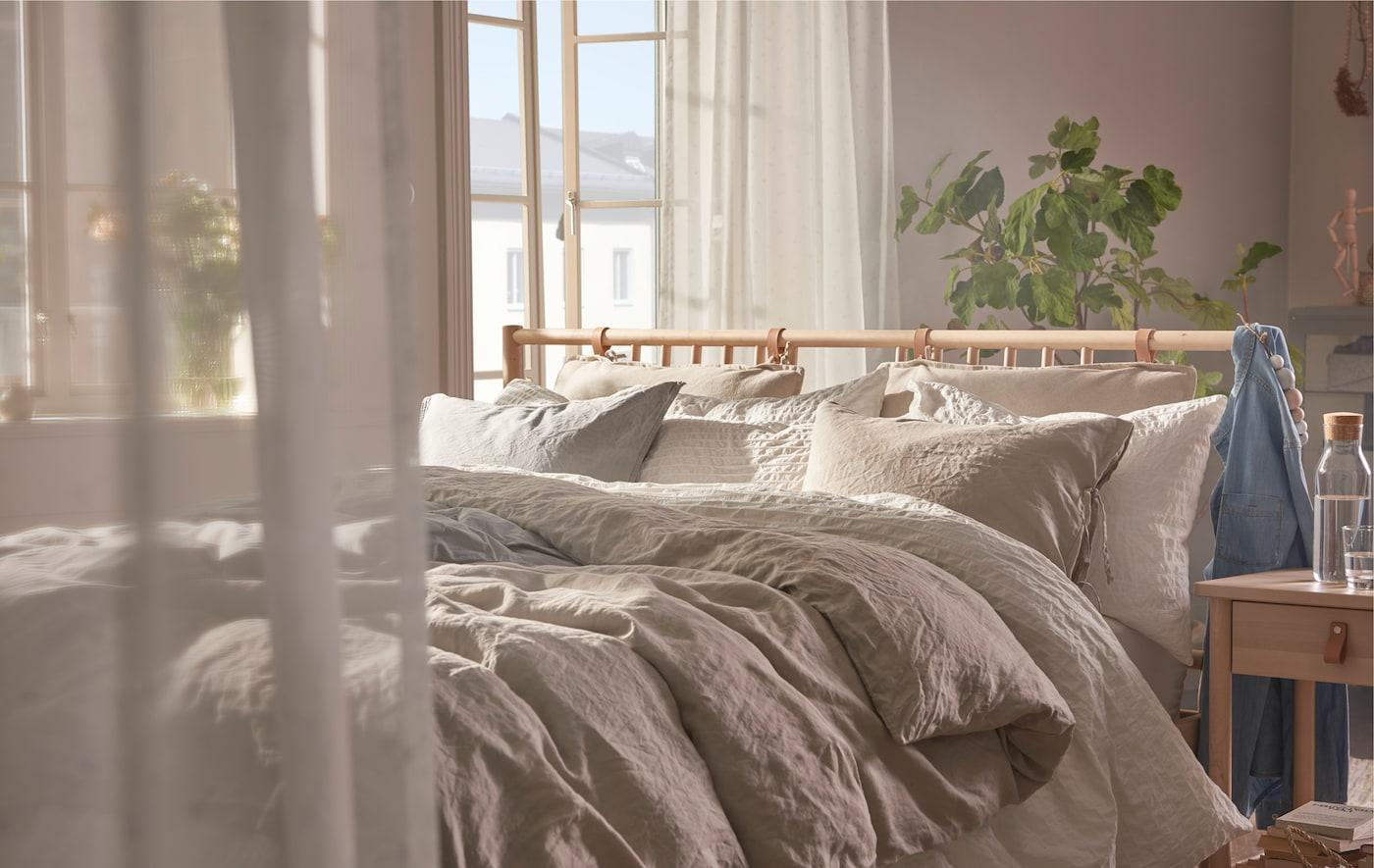 Weich gefiltertes Licht und flauschige Bettdecken sind die perfekte Ergänzung für BJÖRKSNÄS Bettgestell und Ablagetisch aus Birkenholz.
