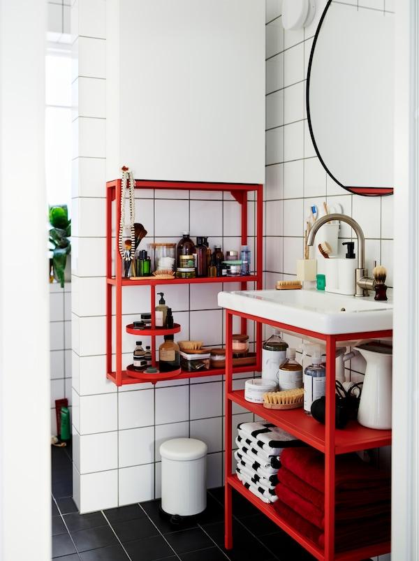 Weiss gekacheltes Badezimmer mit einem Mix aus roten und weissen ENHET-Modulen, in dem Dekorationen und Accessoires untergebracht sind.