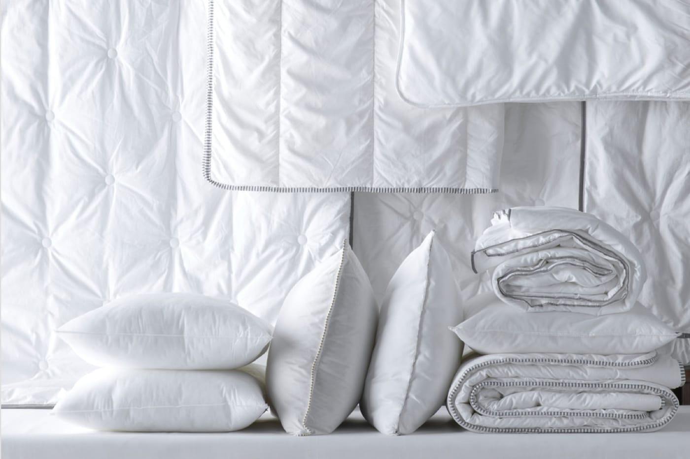 Weiße Kopfkissen und weiße Bettdecken liegen nebeneinander.