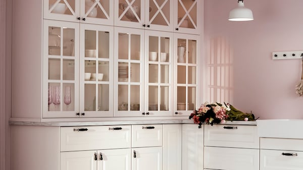 Weiße METOD Küche mit BODBYN Fronten und Vitrinentüren vor einer rosafarbenen Wand