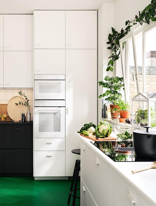 Weiße METOD Küche mit grünem Boden und Pflanzen.