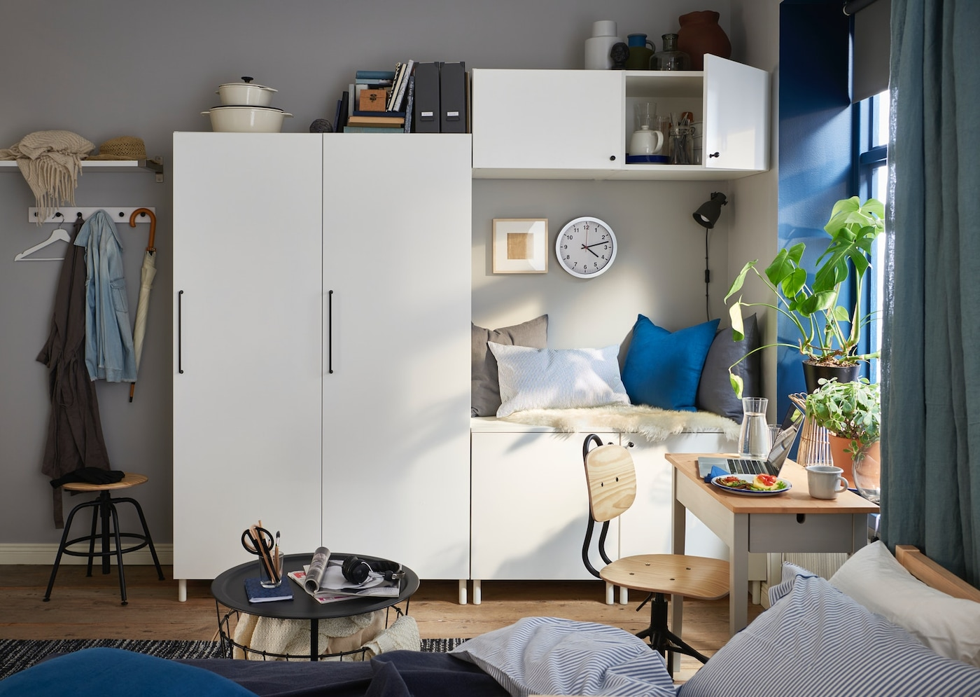 Weiße Schrankkombination von PLATSA in einem Jugendzimmer vor einer grauen Wand