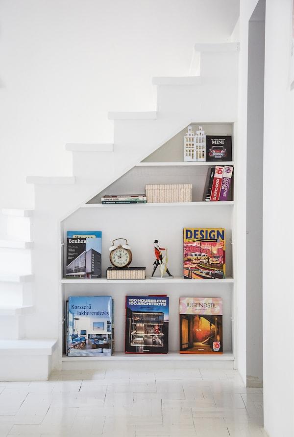 Weißer Treppenaufgang mit eingebautem Regal gefüllt mit Büchern & anderen Gegenständen