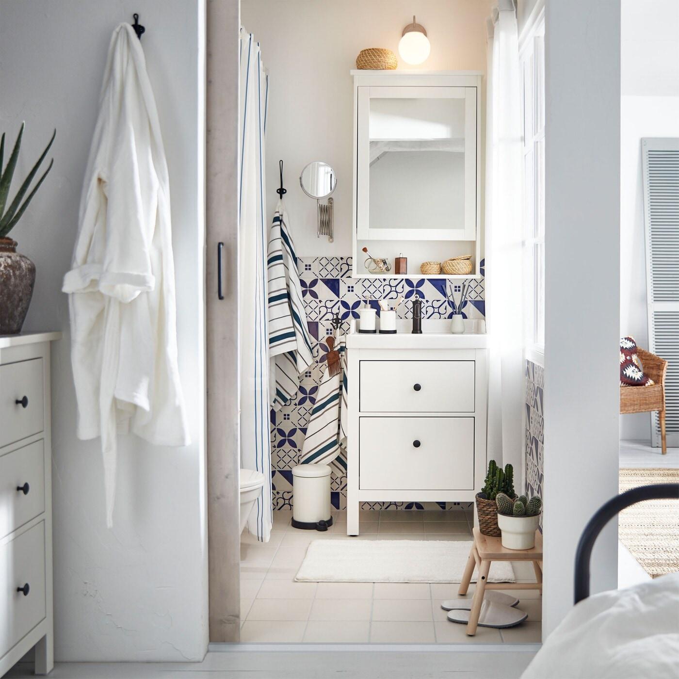 Weißes, schmales Badezimmer mit Kommode, Holzhocker, Seifenspender, Abfalleimer & Blumentopf.