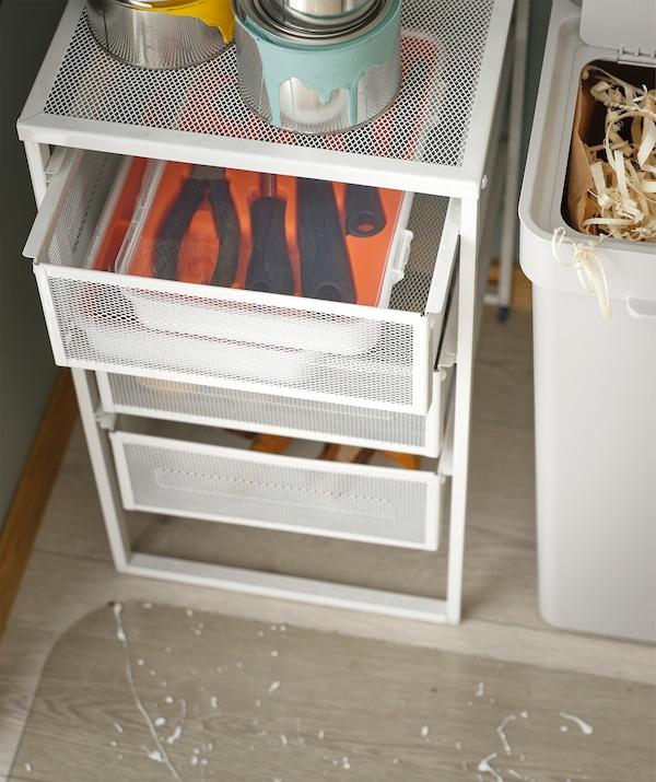 وحدة أدراج LENNART مع أدوات FIXA في الدرج العلوي وعلب طلاء مكدسة في الأعلى، وبجانبها حاوية لإعادة التدوير .
