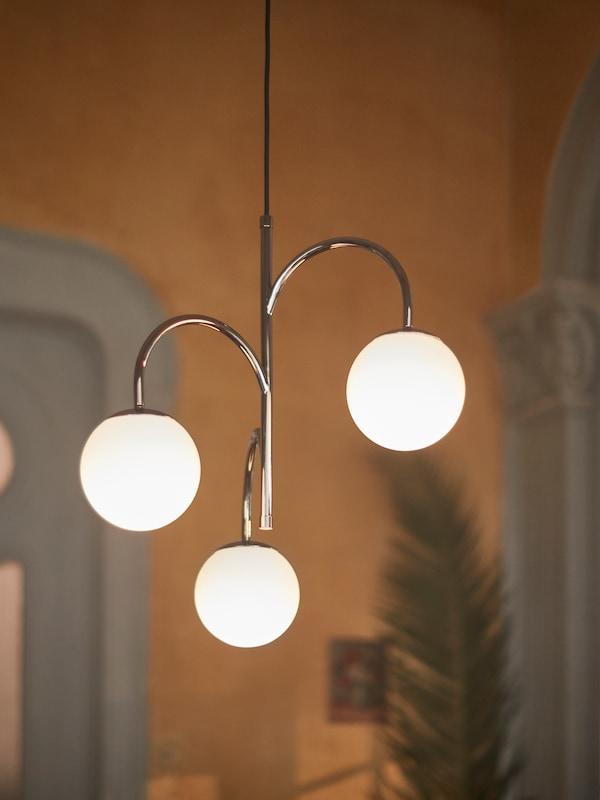 وحدة إضاءة تحتوي على ثلاثة مصابيح معلقة من سقف في غرفة جلوس مع نبات أخضر.
