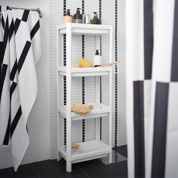 وحدة رفوف بيضاء داخل دوش أبيض/أسود ويتم عليها تخزين مستلزمات الدوش مثل الشامبو وما إلى ذلك.