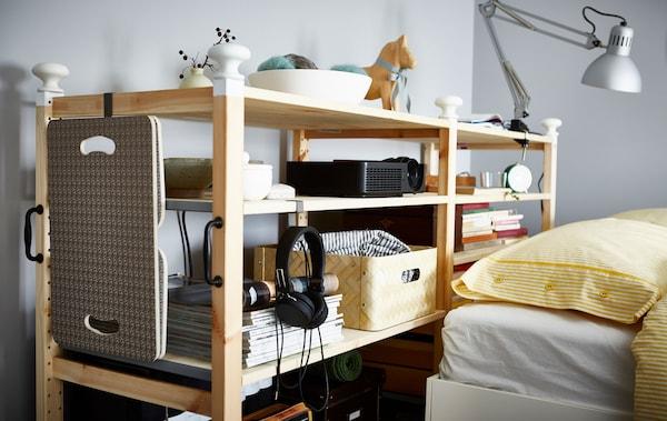 وحدة رفوف IVAR مصممة حسب الطلب تقع خلف سرير.