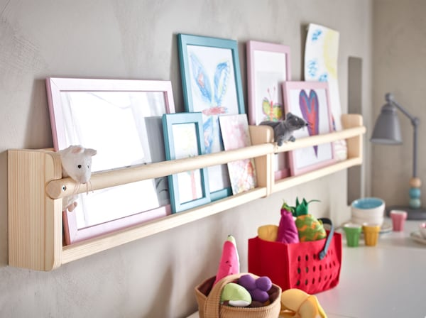 وحدة تخزين جدارية صنوبر FLISAT من ايكيا مع سكة تعليق لتخزين الكتب وإطارات الصور عند تعليقها على الحائط.
