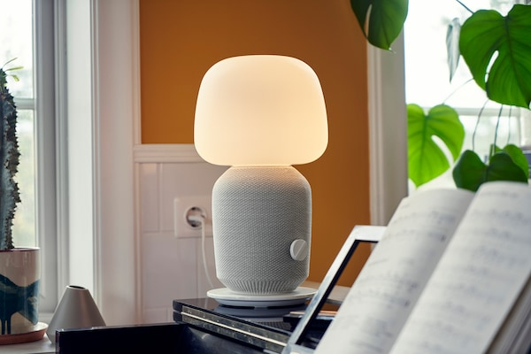 White and gray SYMFONISK lamp speaker standing on a piano, with sheet music in the foreground.