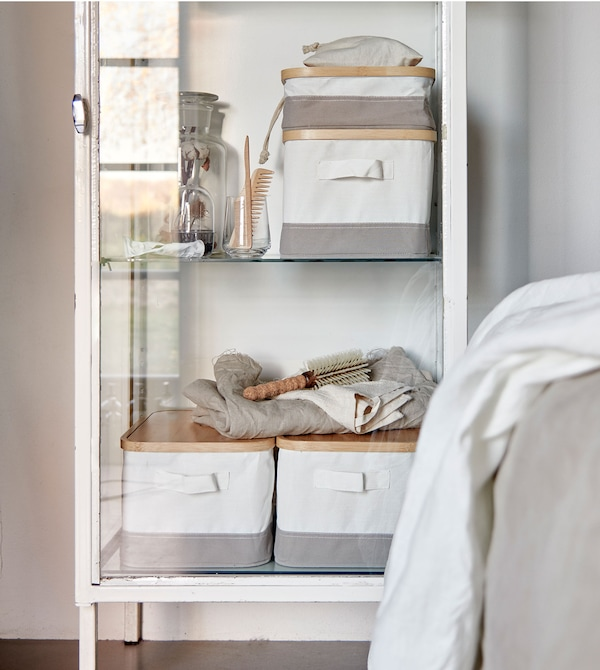 White and grey RABBLA storage boxes made from bamboo and textile, placed in a white, vintage glass door cabinet.