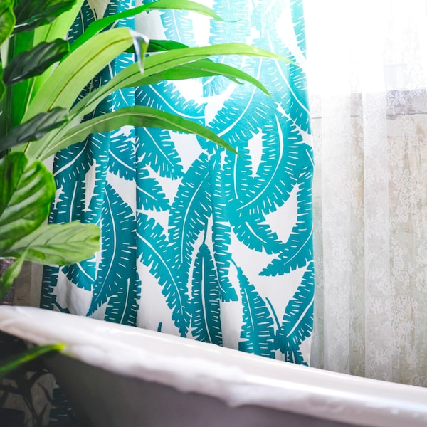 White and turquoise printed fabric is used as a shower curtain around a white bath. A plant is placed next to the bath.