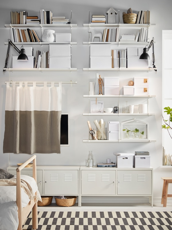 White BERGSHULT/PERSHULT shelves, filled with storage and decorations, and white IKEA PS cabinets cover a bedroom wall.