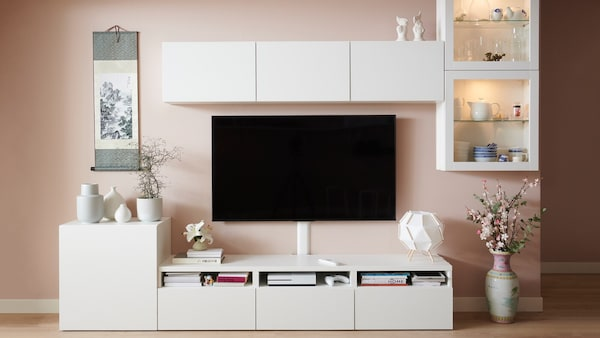 White BESTÅ TV storage unit with shelves and cabinets.