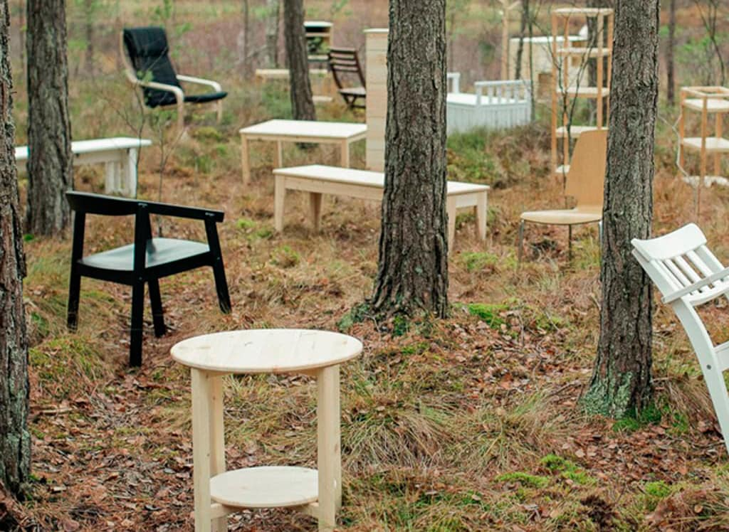 White, black, and light wooden tables and chairs scattered throughout a forest, one source of our renewable materials.