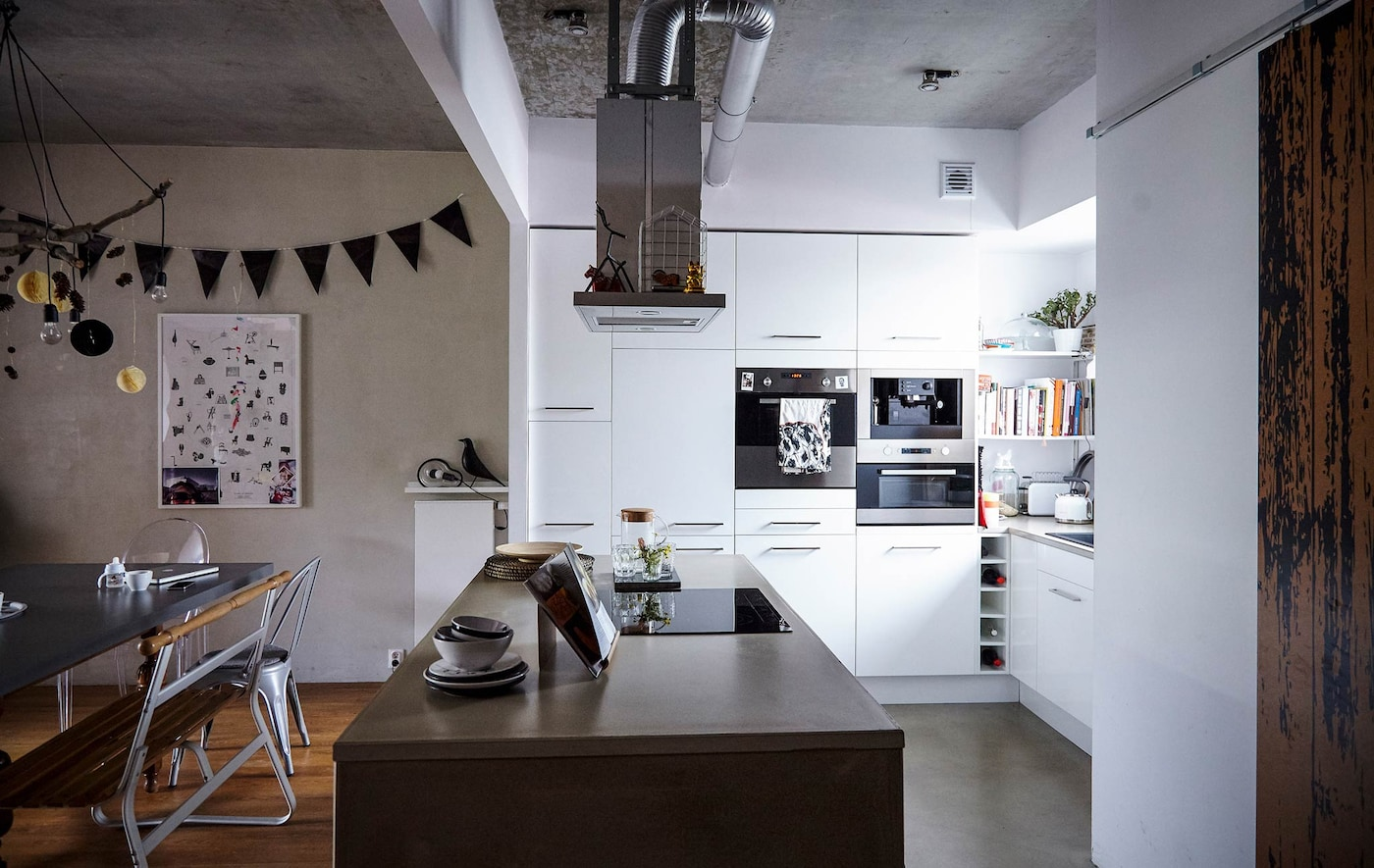 White cabinets and a large kitchen island with concrete counter top in a white, modern kitchen.