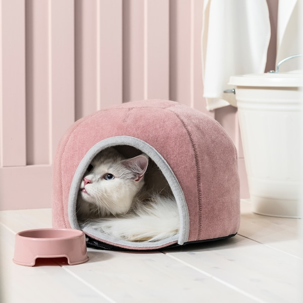White cat peeking out of a round, pink LURVIG cat house made from soft fabric, with a matching pink bowl next to the opening.
