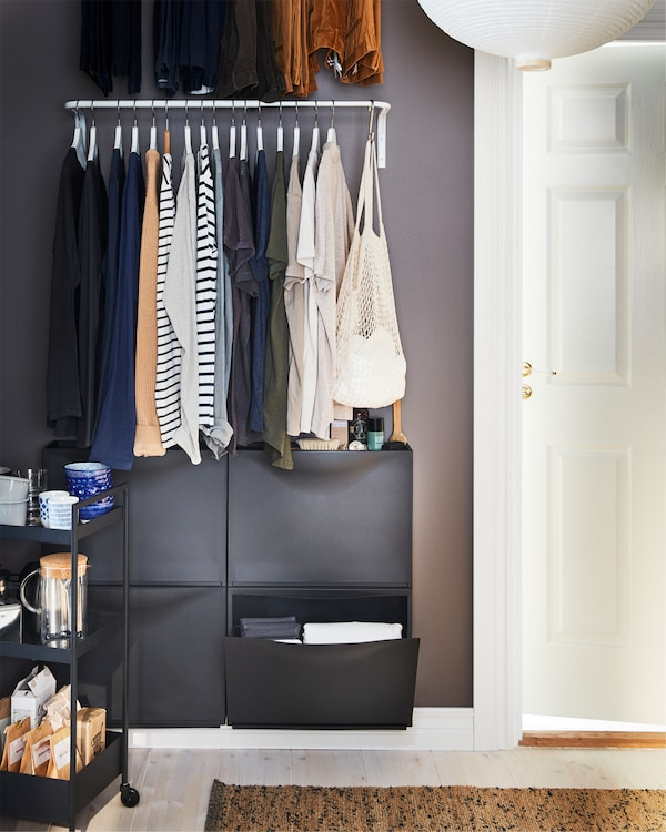 White clothes bar mounted on a wall with hangers with clothes, black wall-mounted shoe cabinets below and a black trolley.