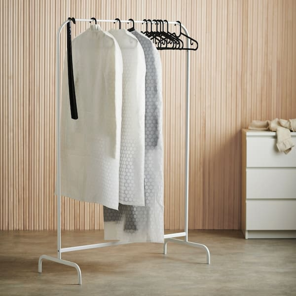 White clothes rack with clothes covers and hangers.