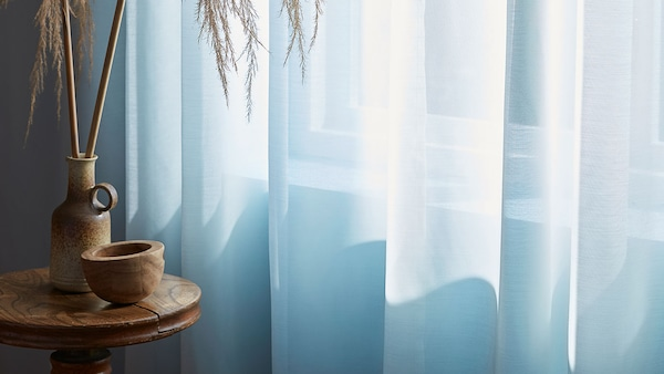White curtains in front of a sunlit window.