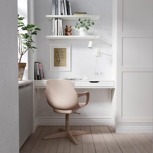 White desk and a beige coloured ODGER swivel chair is placed on the corner of a room.