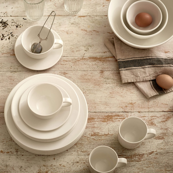 White dinnerware stacked on a wooden table