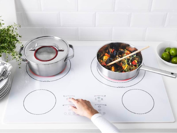 White glass induction cooktop with two pots, one with vegetables. Hand turning on the cooktop.