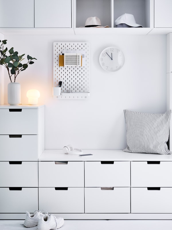 White hallway wall covered in a NORDLI combination. A centred void offers seating surface, a SKÅDIS pegboard and decorations.