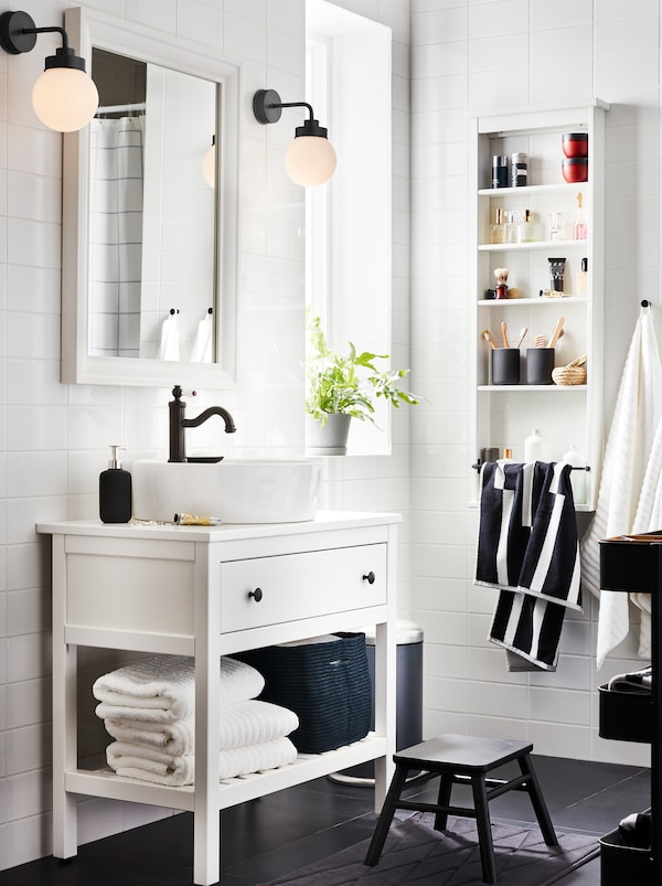 White HEMNES bathroom furniture with one drawer, one shelf with towels and a HAMNSKÄR mixer, a mirror, and two lamps.
