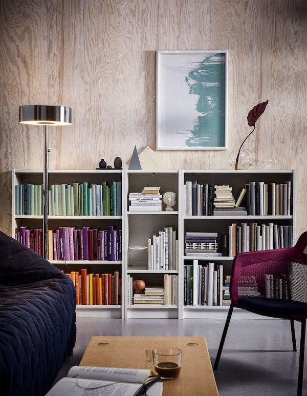 White IKEA BILLY bookcases filled with color coordinated books in a living room.