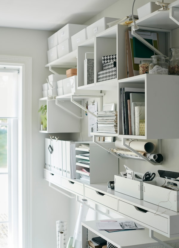 White IKEA EKBY storage cabinets, wall shelves and mounted drawers to organise their office supplies and books.