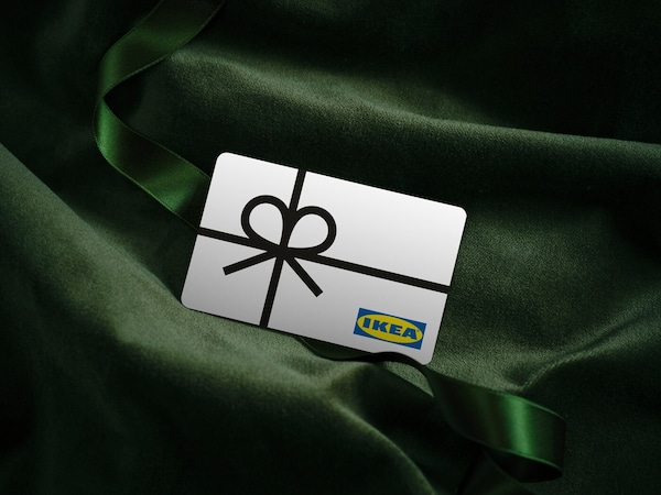 White IKEA gift card with a picture of a black ribbon on top of green velvet fabric.