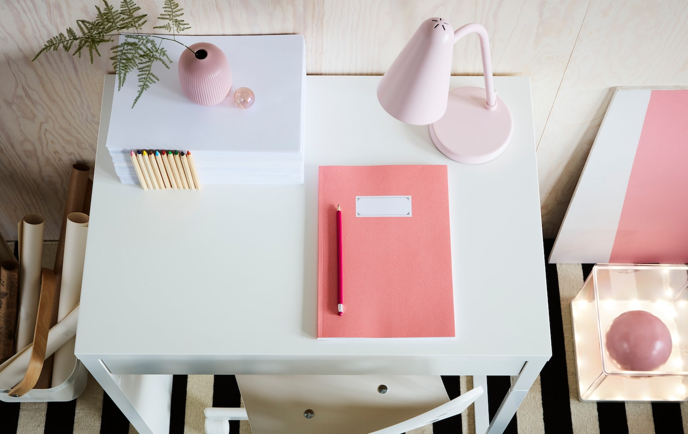 White IKEA MICKE desk with pink notepad, vase and lamp.