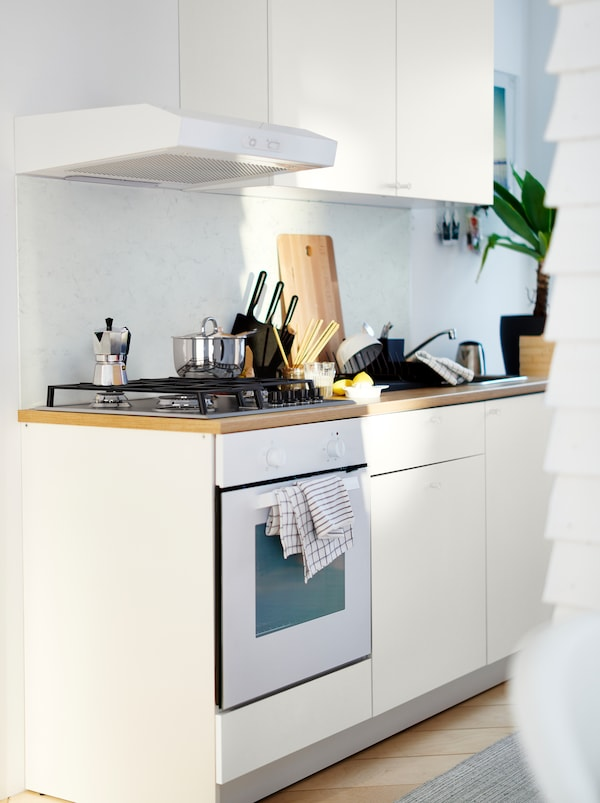 White KNOXHULT kitchenette with a gas-hob oven, a light-wood worktop, pots, knives, a plant and various kitchen accessories.