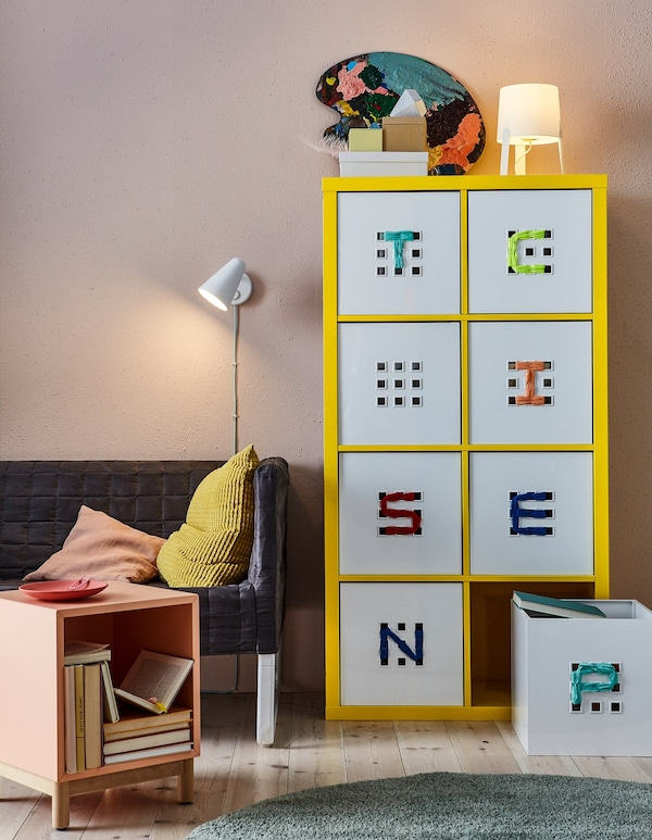 White labelled IKEA LEKMAN storage boxes in a yellow cabinet.