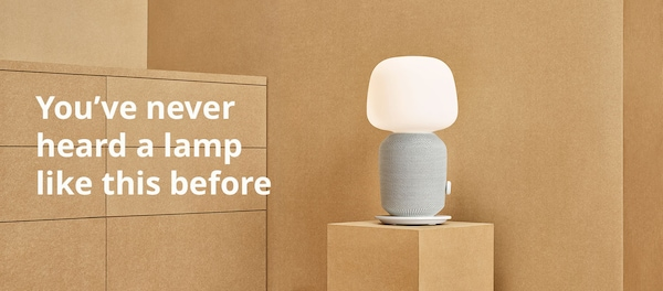 "White lamp placed on a brown cardboard background and a white text saying ""You've never heard a lamp like this before"""