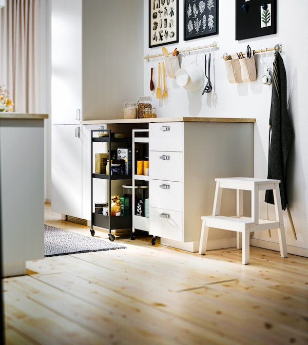 White METOD base cabinets and an EKBACKEN worktop with NISSAFORS trolleys – a black and a white – in a recess below.