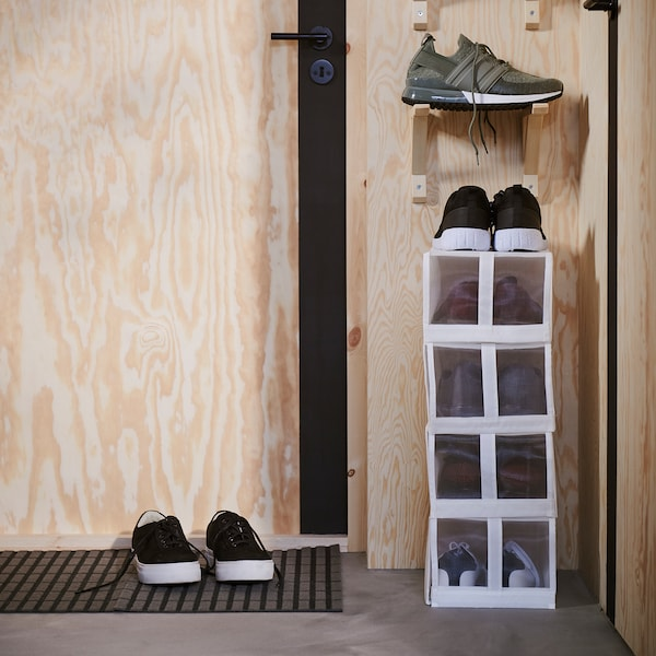 White narrow shoe boxes are stacked on a narrow wall next to a door. Above the boxes are brackets that store more shoes.