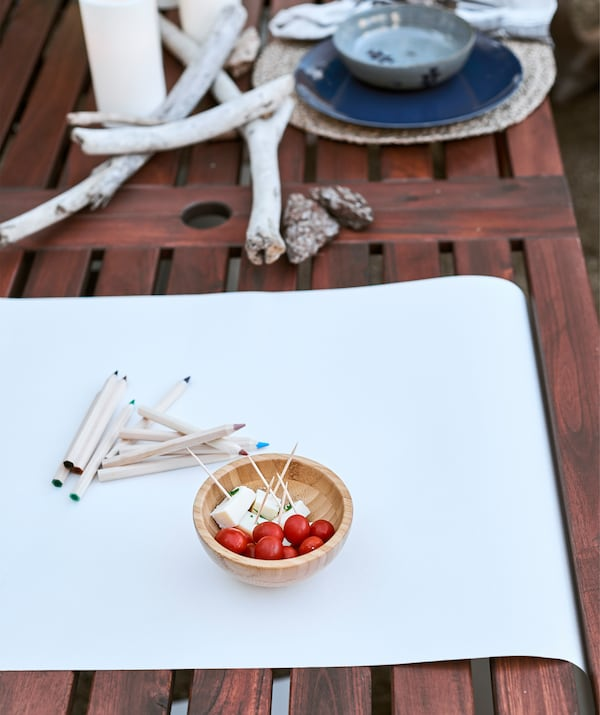 White paper and coloured pencils and a small bowl of snacks on a wooden table, next to driftwood and a place setting.