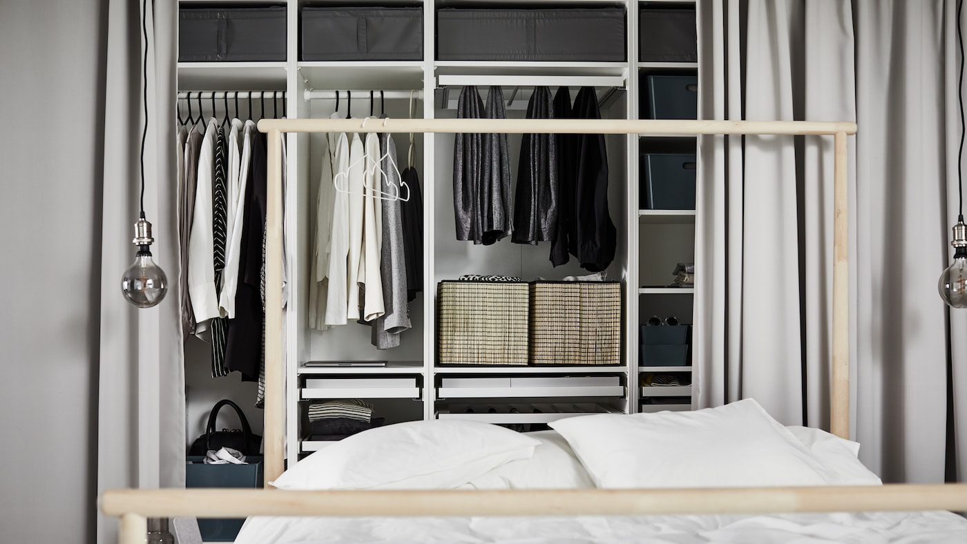 White PAX wardrobe combination containing different sections with multiple clothing items behind a bed with white duvet.
