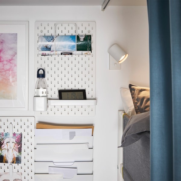 White pegboards are mounted on the wall right next to a loft bed, and they store a water bottle, an alarm clock and more.