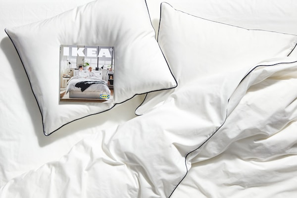 White pillows on a bed with white bed covers, and a copy of the 2020 IKEA Catalogue laying on one of the pillows.